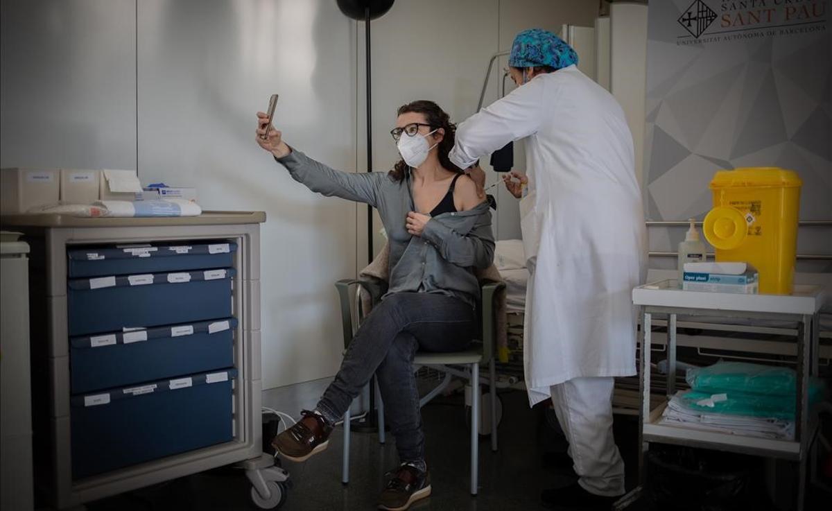 Una enfermera vacuna a una profesional sanitaria con la vacuna de Pfizer-BioNtech contra el COVID-19 en el Hospital de la Santa Creu i Sant Pau de Barcelona.