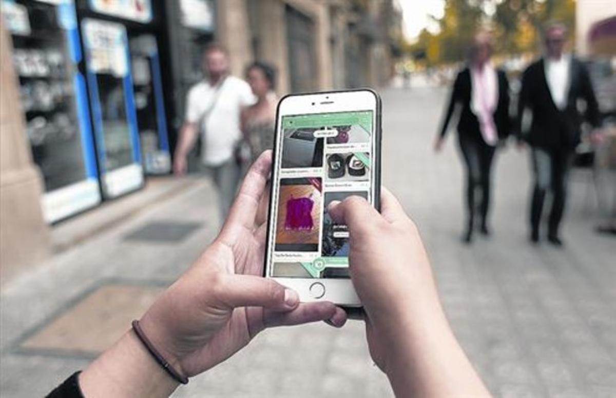Una usuaria consulta la aplicación Wallapop ayer en Barcelona.