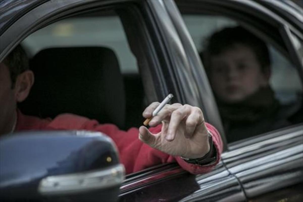 Un conductor fuma un cigarrillo en un coche, con un niño en el asiento de atrás.
