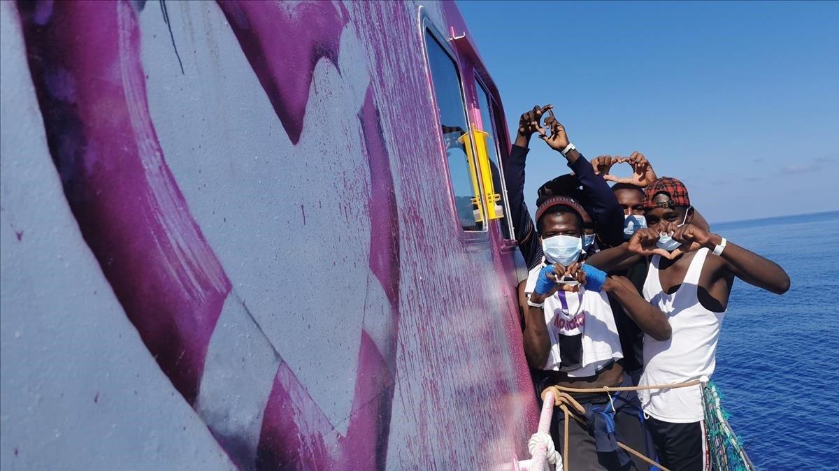 Algunos migrantes junto a la imagen del flotador en forma de corazón en el 'Louise Michel', el barco de salvamento financiadopor de Banksy.