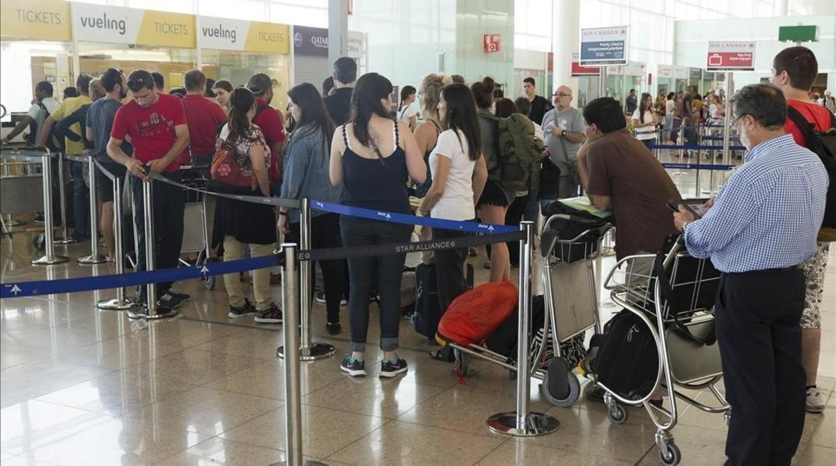 Cola de pasajeros en atención al cliente de El Prat para reclamar retrasos.