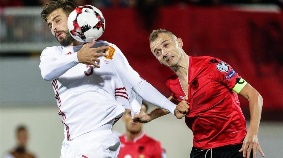 Piqué intenta llevarse el balón junto al albanés Agolli.