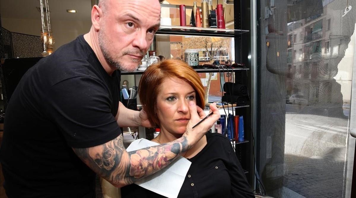 Tomás maquilla a una clienta en su hiperactiva peluquería, en el barrio de Roquetes.