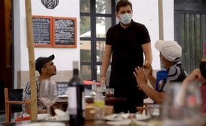 Dos migrantes almuerzan invitados en una terraza de Ceuta.