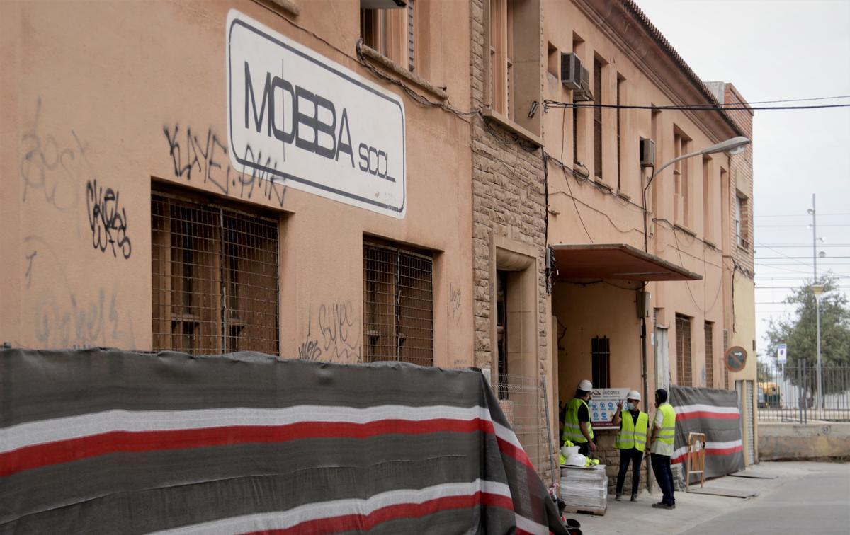 Operarios en el exterior de la fábrica Mobba de Badalona en el primer día de los trabajos previos al derribo de la nave.