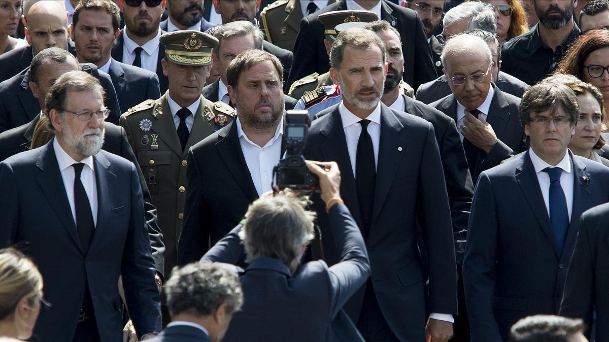 El Rey, junto al 'president', Carles Puigdemont; el vicepresidente del Govern, Oriol Junqueras, y el presidente del Gobierno, Mariano Rajoy, en el minuto de silencio del pasado viernes por las víctimas de los atentados.
