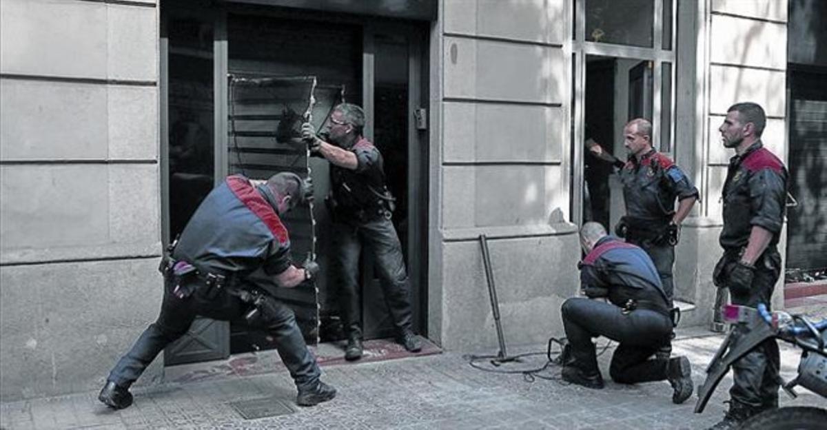 Unos mossosd'esquadraderriban la puerta del club cannábico Hardala en la calle de Bailén de Barcelona, ayer.