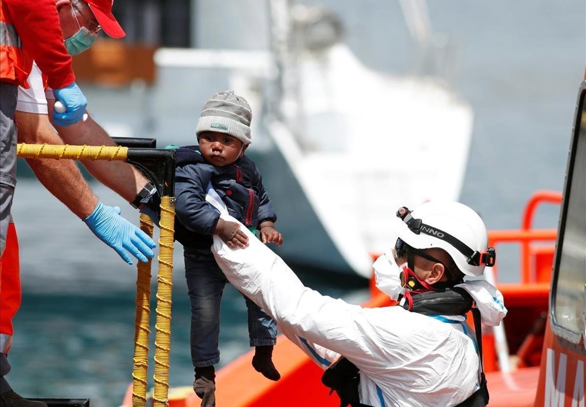 Desembarco de un menor rescatado en una patera a su llegada al puerto canario de Arguineguín.