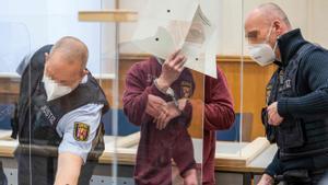 El ex agente del servicio secreto sirio, Eyad al-Gharib, se tapa el rostro con un documento en el tribunal que le ha sentenciado a prisión en Alemania.