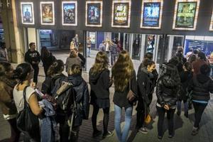 Adolescentes hacen cola para entrar en un cine en Barcelona.