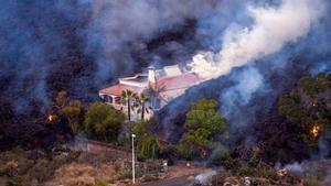 La lava ralentiza su avance destructivo en la isla de La Palma. En la foto, una casa se salva in extremis de ser destrozada por la lava del volcán.