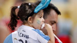 Una niña con la camiseta de Uruguay, junto a su padre.