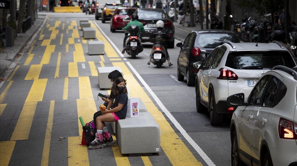 Dos niños descansan en uno de los polémicos bloques de hormigón en forma de banco ubicados en la calle de Consell de Cent.