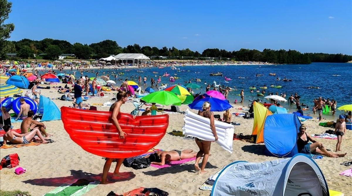 Numerosas personas disfrutan del buen tiempo en el Blue Lagoonde Wachtendonk, Alemania, ayer.
