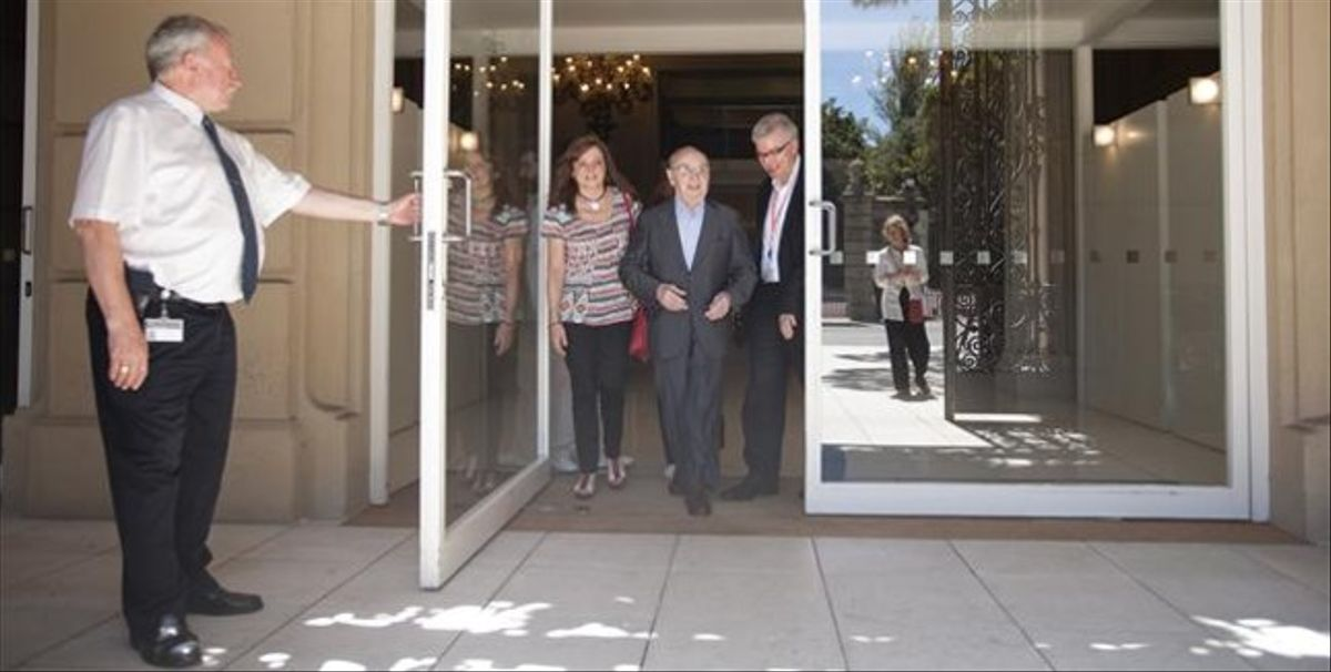 El fotógrafo Joan Colom sale del MNAC acompañado de su hija.
