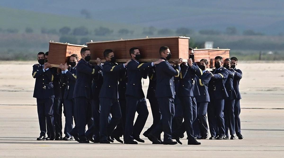 Varios militares llevan a hombros los féretros con los restos mortales de los periodistas David Beriain y Roberto Fraile y del conservacionista irlandés Rory Young asesinados durante la grabación de un documental en Burkina Faso, a su llegada a la base aérea de Torrejón de Ardoz.