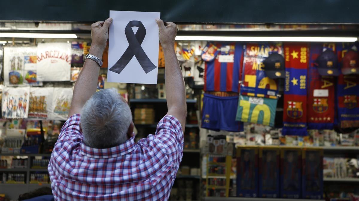 Un quiosquero de laRambla, coloca un lazo simbólico en memoria de las víctimas.