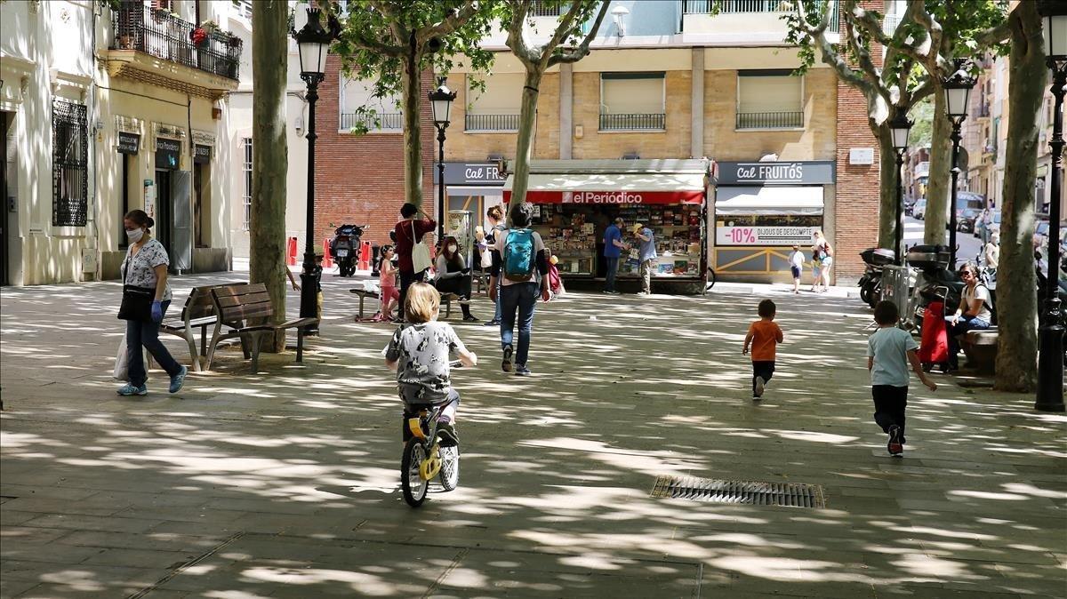 Un grupo de niños juega en las calles de Barcelona junto a los comercios cerrados durante el estado de alarma