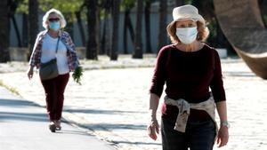 Dos mujeres pasean con mascarilla en Madrid.