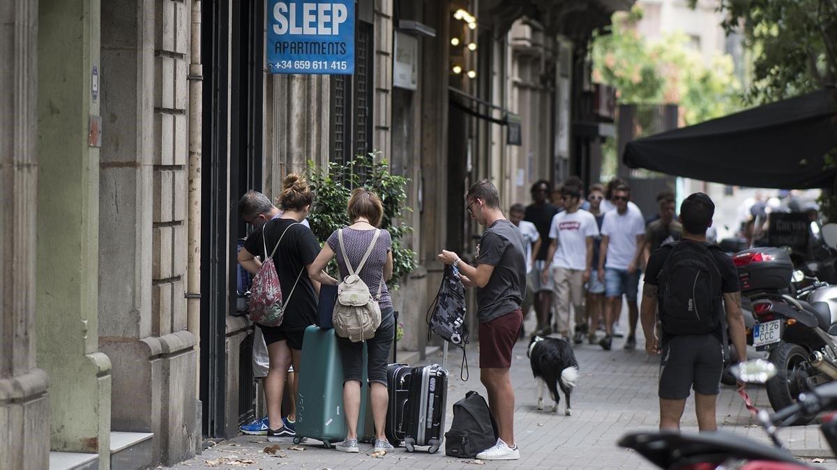 Un grupo de turistas entra en una finca de apartamentos turísticosel pasado agosto.