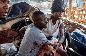 Un hombre ayuda a un herido a salir de una de las zonas conflictivas en el marco de las protestas por el resultado de los comicios en Zimbabue.