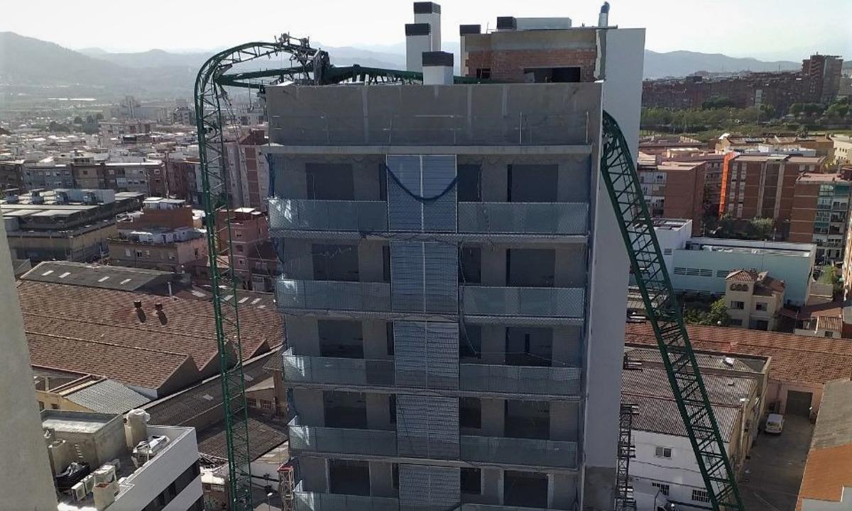 Una grua desplomada sobre un edificio de viviendas en Cornellà de Llobregat.