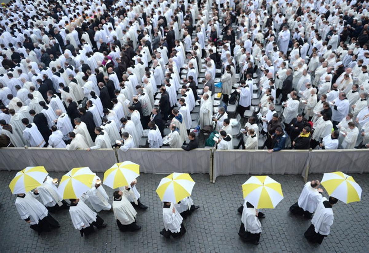 Sacerdotes, con paraguas de los colores del Vaticano, en la Plaza de San Pedro.