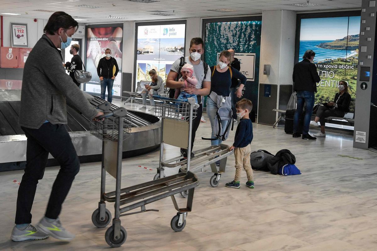 Turistas llegan al aeropuerto griego de Heraklion para iniciar sus vacaciones en la isla de Creta.