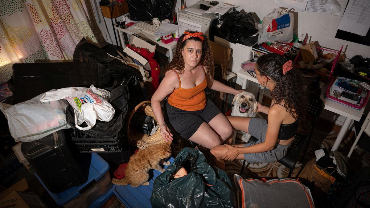 Mimi, ayer junto a su hija Marina, de 22 años, y su perra de asistencia, en el salón de su casa de Sants y rodeadas de bolsas ante un posible desahucio.