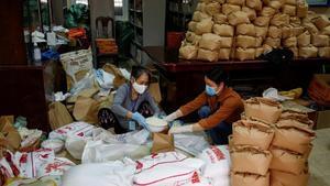 Dos mujeres empaquetan arroz para donarlo a los más vulnerables, en Hanoi.