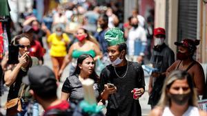 Dos jóvenes usando mal la mascarilla en Brasil.