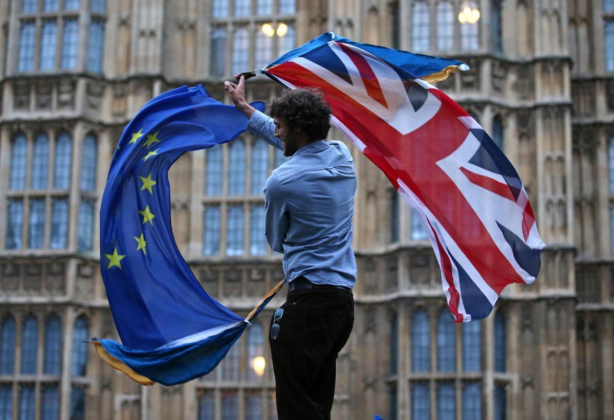 Un joven ondea las banderas británica y europea frente al Parlamento del Reino Unido.