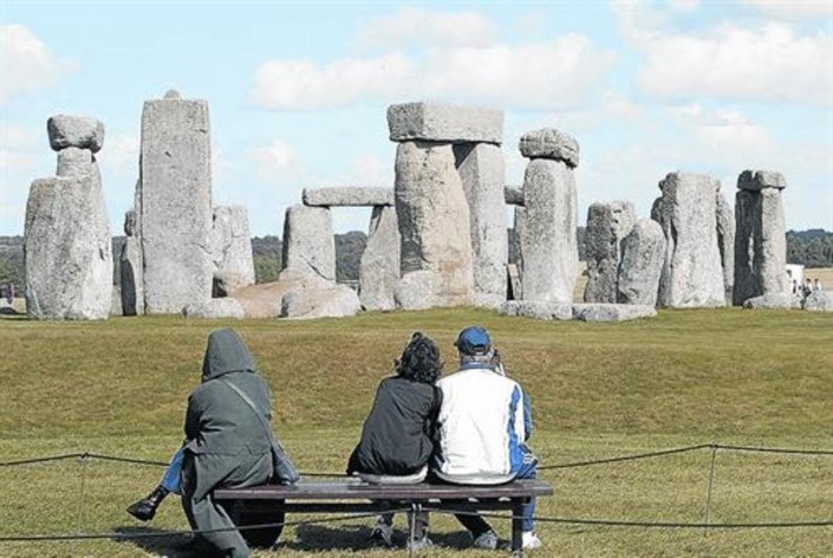 Unos turistas contemplan el monumento megalítico circular de Stonehenge.