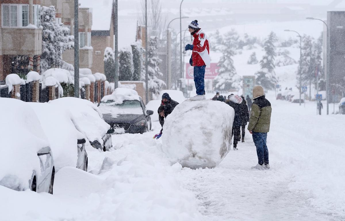 Unos jóvenes hacen una gran bola de nieve durante el temporal de nieve en Madrid por la borrasca Filomena.