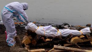 Un hombre protegido con un traje EPI, junto al cadáver de un familiar fallecido por culpa del coronavirus antes de su cremación en el río Ganges, en la India, el pasado 6 de mayo.