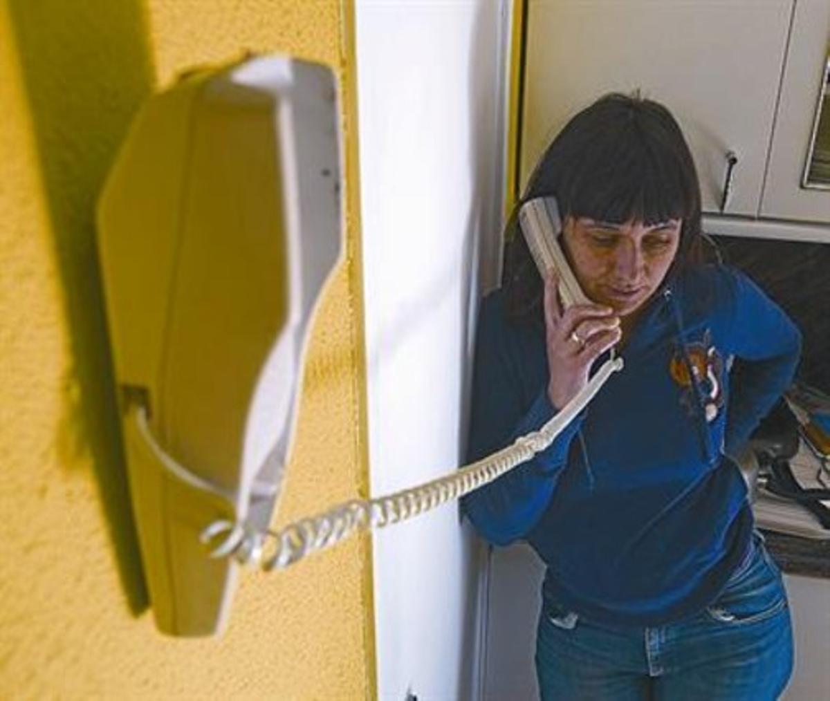 Una mujer habla utilizando un teléfono fijo.