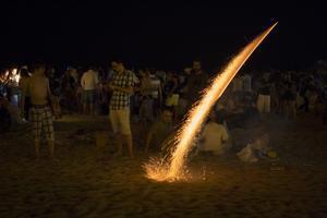 Un petardo encendido elevándose en la playa de la Nova Icària