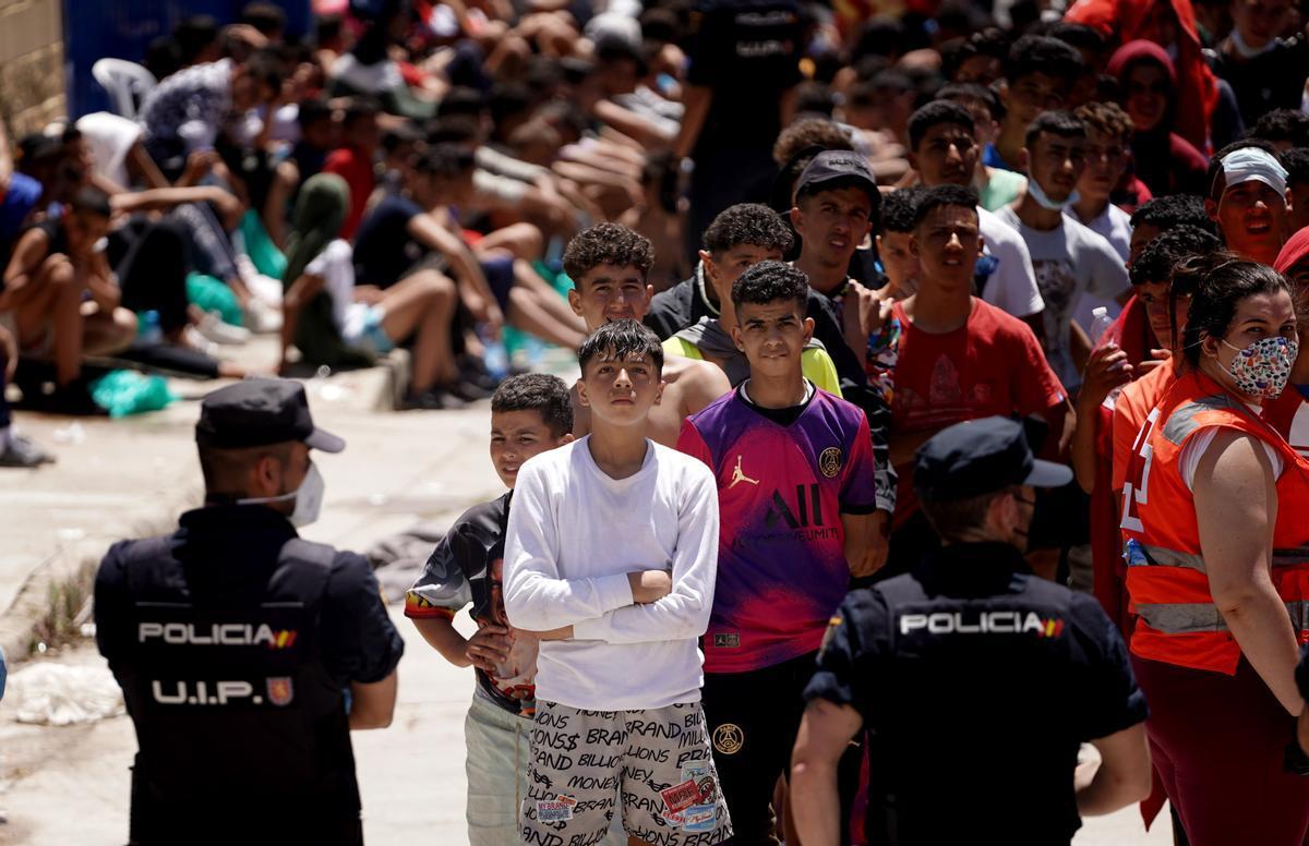 Menores migrantes no acompañados son custodiados por la policía en las naves industriales de Ceuta.