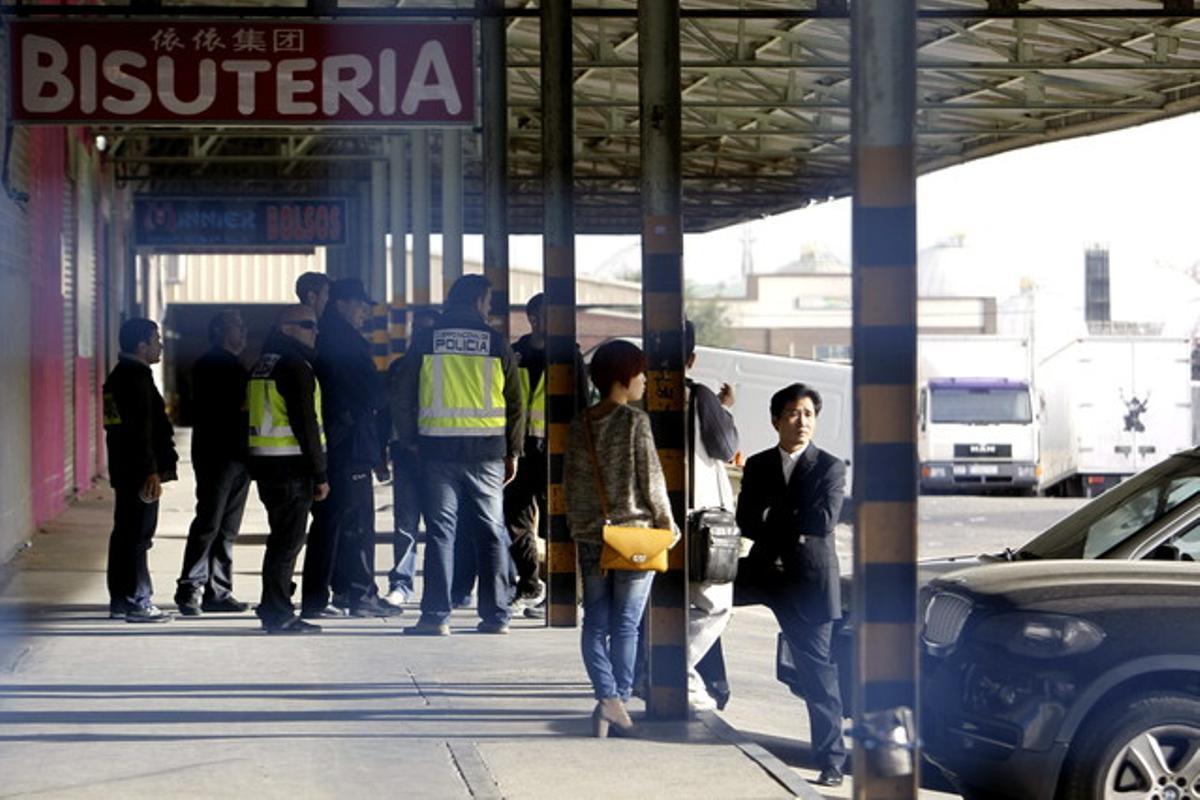 Agentes de la Policía Nacional y ciudadanos chinos, durante el registro a negocios en el polígono industrial Cobo Calleja, en Fuenlabrada.
