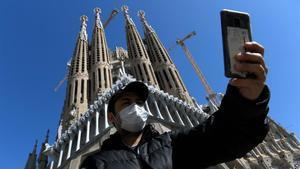 Un turista se hace un selfie ante la Sagrada Família ataviado con una mascarilla.