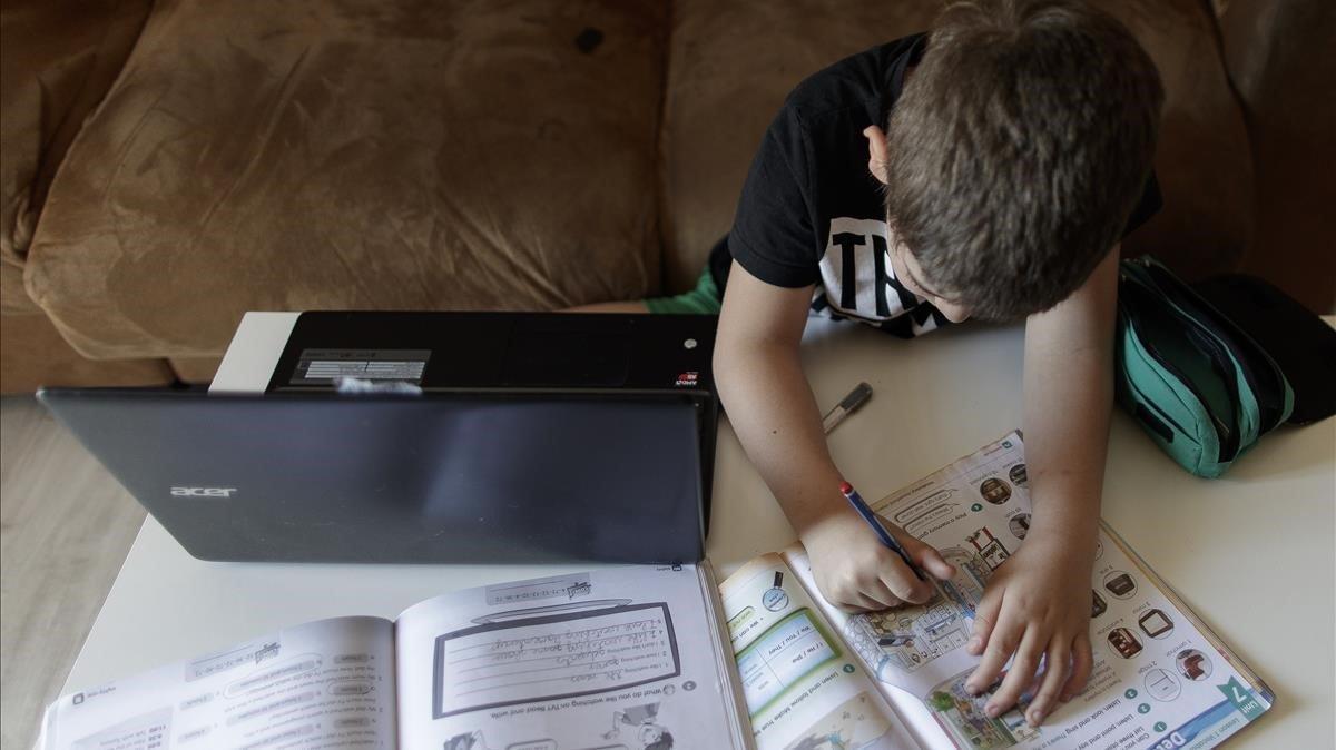 Un niño usa un ordenador como apoyo para hacer sus deberes, durante el confinamiento.