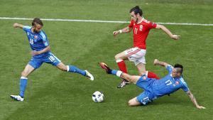 Bale conduce el balón perseguido por dos rivales en el partido inaugural de Gales