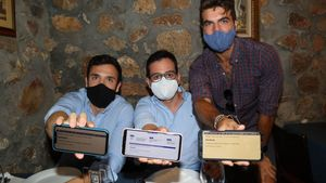 Tres clientes muestran sus certificados en un bar.