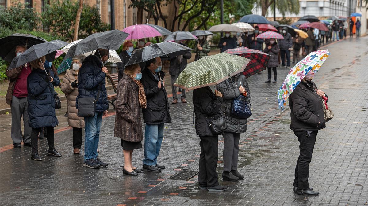 Colas con paraguas en el exterior de las mesas electorales de la Escola Industrial.