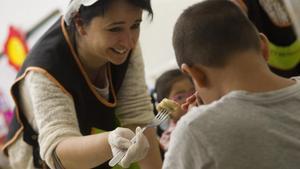 Una monitora ayuda a un niño en un comedor escolar.