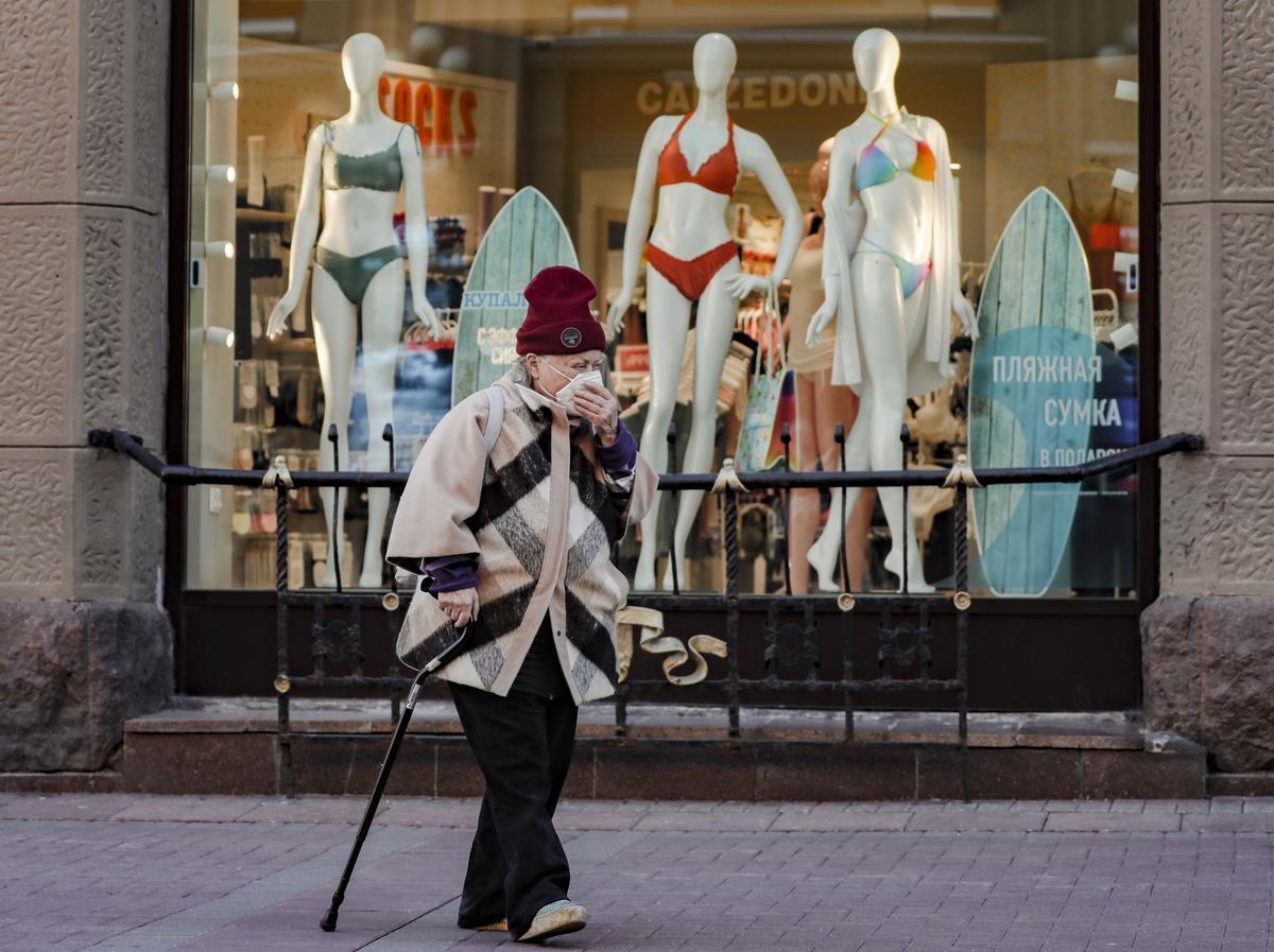 Una mujer con mascarilla camina por una calle comercial de Moscú.