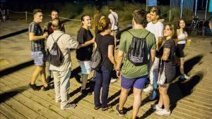 Varios mediadores, con mochilas negras, hablan con jóvenes de botellón en Castelldefels.
