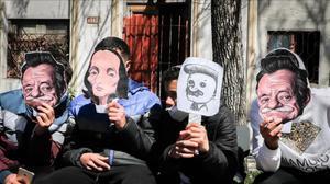 Estudiantes sostienen caretas con caricaturas de Mario Benedetti.