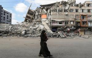 Una mujer palestina con su hijo huye de su hogar durante los ataques aéreos israelís, en Gaza.