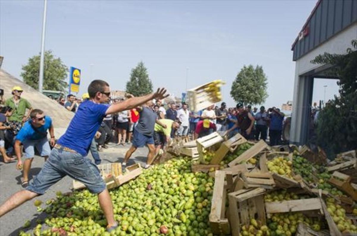 Unos payeses lanzan peras a las puertas de un híper en Lleida